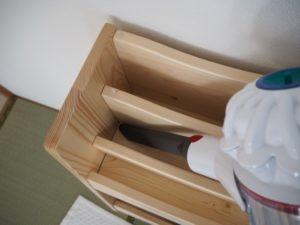 「ダイソン V7 Mattress」の隙間ノズルで本棚の隙間を掃除している画像